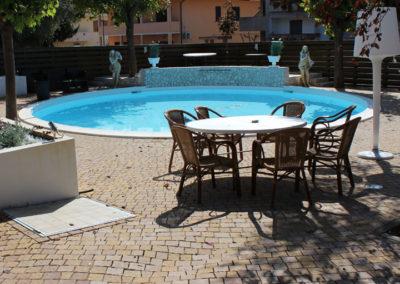 piscina-con-statue-e-verde